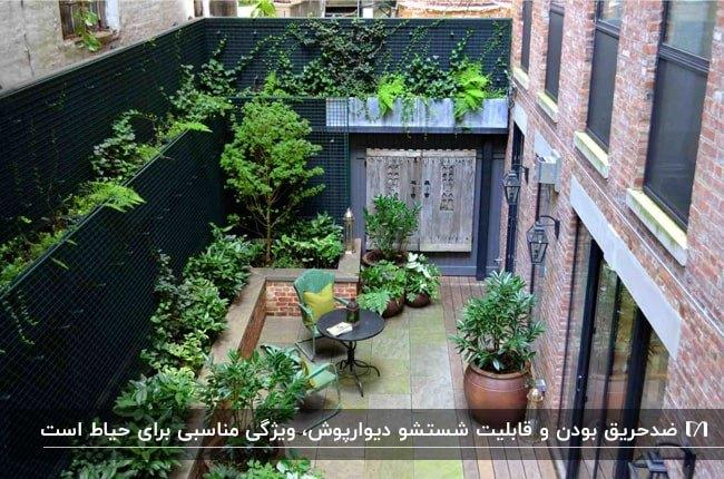 تصویر حیاطی سرسبز با دیوارپوش های مشکی و میز و صندلی و گلدان های گل