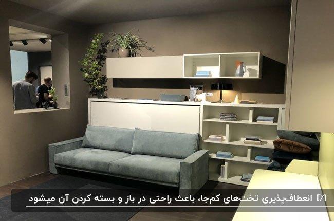مبل و تخت تاشو آبی رنگ برای سوئیت دانشجویی کنار قفسه کتاب