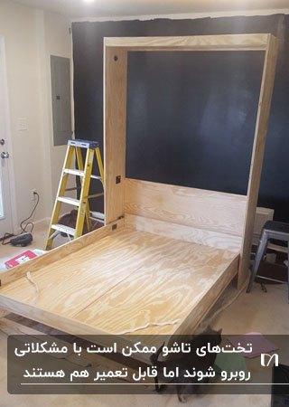 یک تخت چوبی تاشو دیواری در حال تعمیر مقابل دیوار سرمه ای رنگ