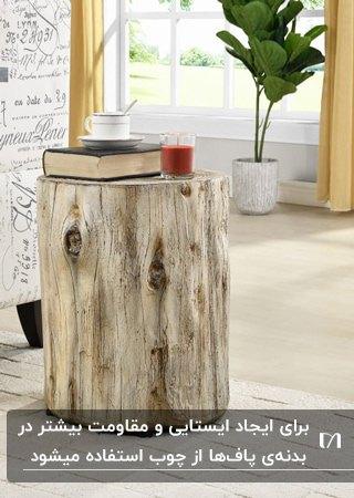 تصویر یک پاف دایره ای از چوب طبیعی با کتاب و لیوان روی آن