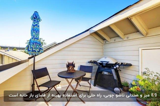 تصویر یک روف گاردن کوچک با یک میز گرد و دو صندلی تاشوی چوبی و سایبان چتری آبی