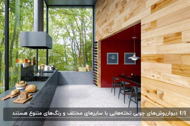 تصویر آشپزخانه ای با کانتر خاکستری و دیوارپوش چوبی مقابل دیوار شیشه ای رو به جنگل