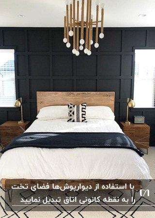تصویر اتاق خوابی با تخت و پاتختی های چوبی، دیوارپوش مشکی و روتختی و بالشت های سفید و لوستر آویز