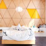 تصویر یک اتاق خواب با تخت چوبی، دو قفسه اطراف تخت به عنوان پاتختی و دیوارپوش مثلثی چوبی و زرد