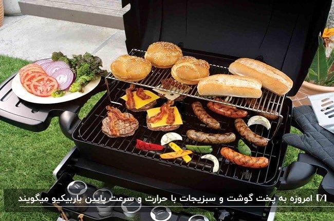 تصویر یک باربیکیو درب دار مشکی در حیاط با سوسیس و سبزیجات و نان در حال پخت