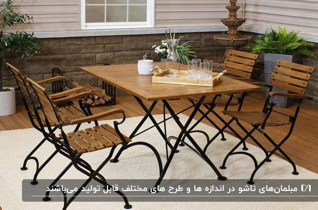 میز و صندلی چهارنفره چوبی با پایه های فلزی در حیاط خانه