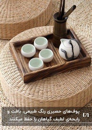 تصویر یک پاف حصیری با ارتفاع کم با سینی چوبی و فنجان سرامیکی روی آن