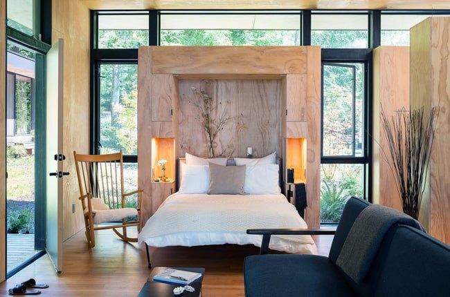 نشیمنی به سبک مدرن با یک تخت دو نفره تاشو کنار یک صندلی راک چوبی