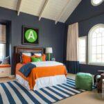 اتاق خوابی با تخت نارنجی و آبی، پاف سبز و دیوارهای سرم ای و فرش راه راه سفید و آبی
