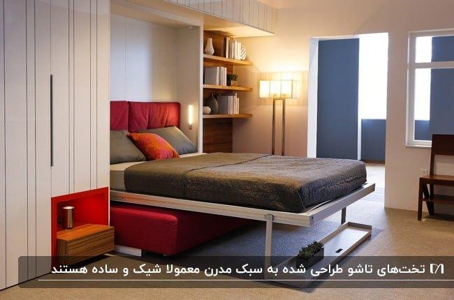 تصویر یک اتاق به سبک مدرن با تخت تاشوی خاکستری با کوسن قرمز، کاناپه قرمز زیر تخت و آباژور ایستاده