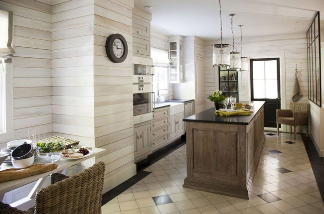 تصویر آشپزخانه ای با دیوارپوش چوبی رنگ روشن با جزیره تیره