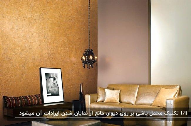 نشیمنی با مبل طلایی، چراغ آویز مشکی و تابلویی مقابل دیوار مخمل پاشی شده نارنجی