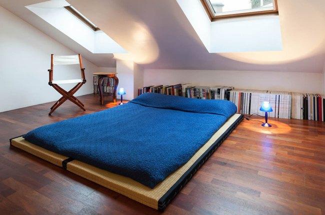 اتاق زیرشیروانی با کفپوش چوبی، قفسه کتاب، صندلی تاشو و تخت کم ارتفاع آبی