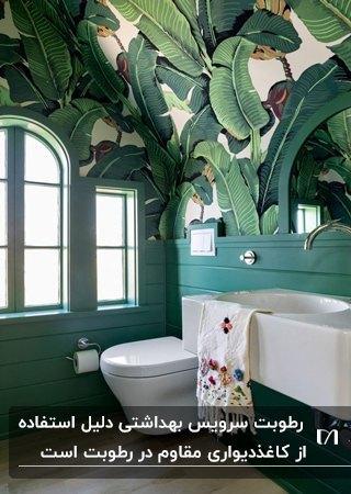 یک سرویس بهداشتی با دیوارهای سبز تیره و کاغذدیواری طرحدار سفید با برگ های سبز برای سقف