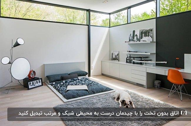 اتاق خوابی بدون تخت با قفسه های چوبی روی دیوار، و فرش نرم طوسی با یک سگ سفید