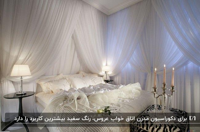 اتاق خواب عروسی با تخت خواب و روتختی سفید، پرده های حریر سفید، شمع و مروارید و آباژورهای سفید