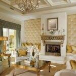 دکوراسیون نشیمن کلاسیکی با لوازم سفید و طلایی و لمسه کاری طلایی دیوارهای اطراف شومینه