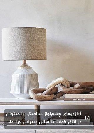 تصویر یک آباژور رومیزی شیری رنگ از جنس سرامیک در کنار اکسسوری چوبی و کتاب