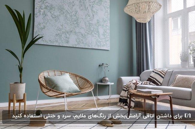 دکوراسیون داخلی نشیمن با ترکیب رنگ دیوار سبز، مبل طوسی، میز چوبی و صندلی حصیری