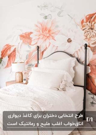 اتاق یک دختر نوجوان با تخت فلزی تک نفره و کاغذدیواری با گل های گلبهی و نارنجی