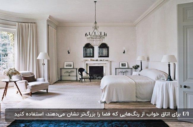 دکوراسیون اتاق خواب بزرگی به رنگ کرم با تخت، لوستر ، آباژور پایه بلند و دیوار شیشه ای