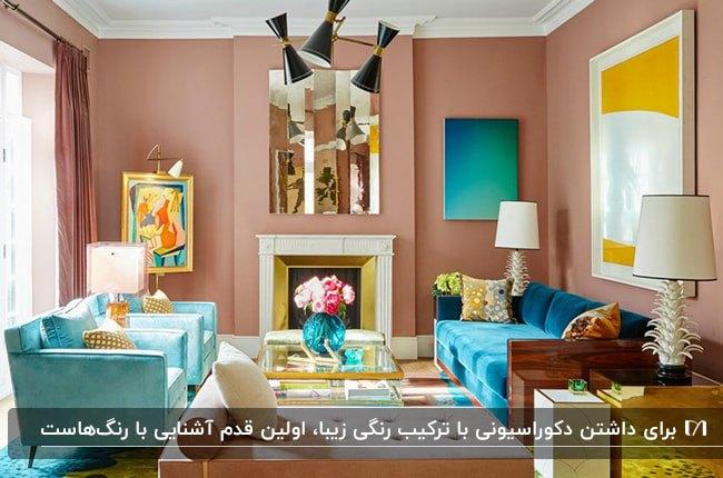دکوراسیون داخلی نشیمن با ترکیب رنگ دیوار بژ، مبل آبی، پاف صورتی و میزهای طلایی