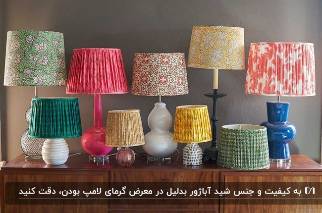 تصویر یک میز کنسول چوبی با انواع آباژورهای رومیزی با شیدهای رنگی روی آن