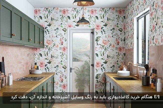 آشپزخانه ای با کابینت های سبز تیره و کاغذدیواری با گلهای صورتی و برگ های سبز