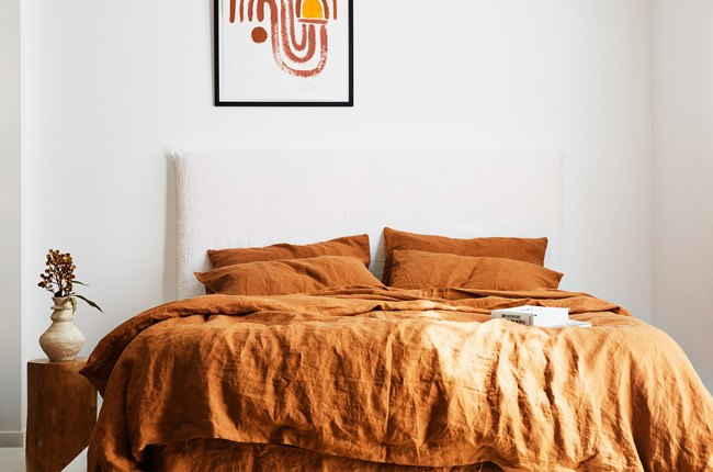 دکوراسیون یک اتاق خواب با تخت دو نفره سفید و روتختی قهوه ای با یک گلدان کوچک کنار تخت