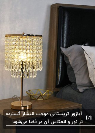 یک آباژور کریستالی با پایه طلایی کنار تخت خواب چوبی