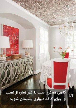 اتاق غذاخوری با میز سفید، صندلی های سفید و قرمز، کنسول آینه ای و سقفی با کاغذدیواری طرحدار قهوه ای