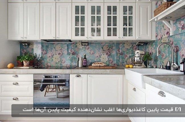آشپزخانه ای با کابینت های سفید کلاسیک و کاغذدیواری گلدار بین کابینتی با زمینه آبی