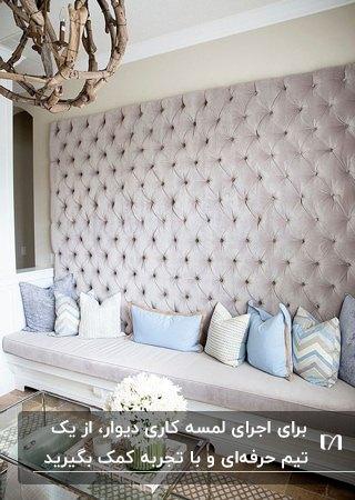 دکوراسیون گوشه ای یک خانه با دیوار لمسه کوبی یاسی و نیمکت همرنگش با کوسن های آبی