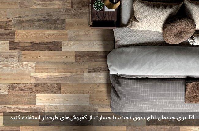 نمای بالای اتاقی بدون تخت با پتوی طوسی و کفپوش چوبی قهوه ای