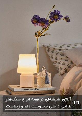 یک آباژور رومیزی شیشه ای سفید کنار تخت خواب به همراه به همراه کتاب و گلدان گل