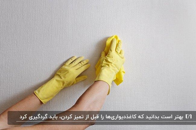 تصویر دو دست با دستکش زرد رنگ، در حال گردگیری کاغذدیواری سفید رنگ
