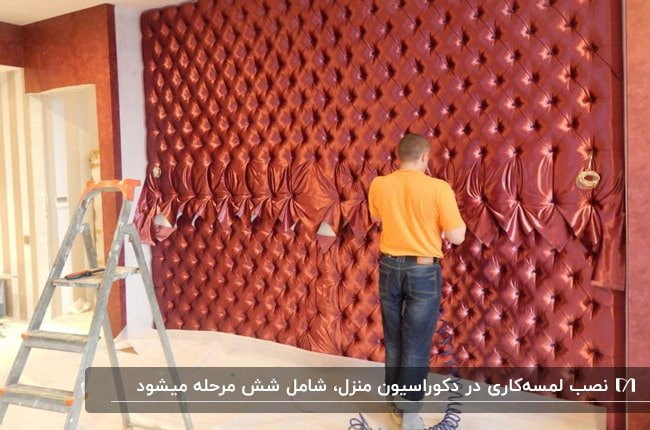 تصویر مردی در حال نصب لمسه کاری قرمز رنگ روی دیواری بزرگ
