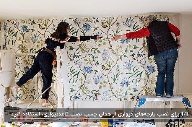 تصویر دو زن در حال نصب پارچه دیواری با طرح های سبز و آبی