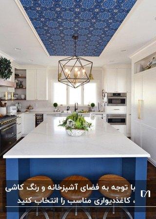 آشپزخانه ای با کابینت های سفید، کانتر آبی، صندلی های چوبی کانتر و کاغذدیواری طرحدار آبی برای سقف