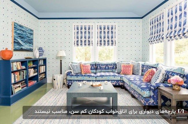 نشیمنی با مبل ال شکل، کوشن های صورتی و آبی و پارچه های دیواری سفید با طرح های آبی