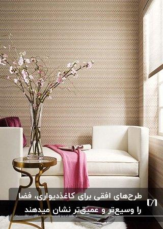 نشیمنی با کاغذدیواری طرحدار افقی کرم رنگ، کاناپه سفید و شال مبل سرخابی و گلدان شیشه ای گل