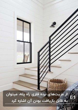 راه پله ای به رنگ سفید با پله های چوبی و نرده های فلزی مشکی