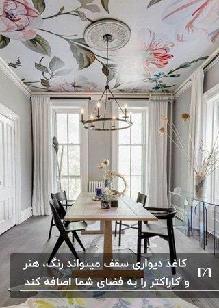 تصویر یک اتاق غذاخوری با میز و صندلی های غذاخوری، لوستر گرد آویز و کاغذدیواری گلدار سقف