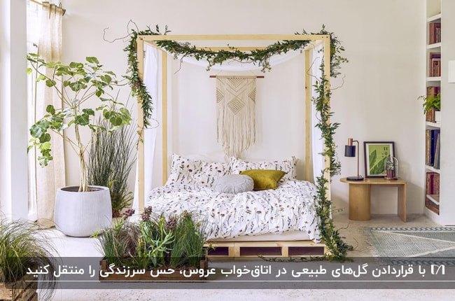 اتاق خواب ساده تازه عروسی با تخت چوبی و گلدان های طبیعی گل و گیاه برای طراوت