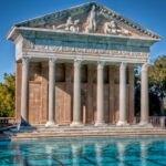 تصویر یک سازه سنگی به سبک رومی با شش ستون کار شده کنار استخر در فضای باز