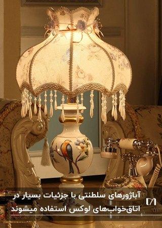 آباژوی سلطنتی به رنگ سفید با طرح های اصیل و آویزهای کریستالی روی میزی