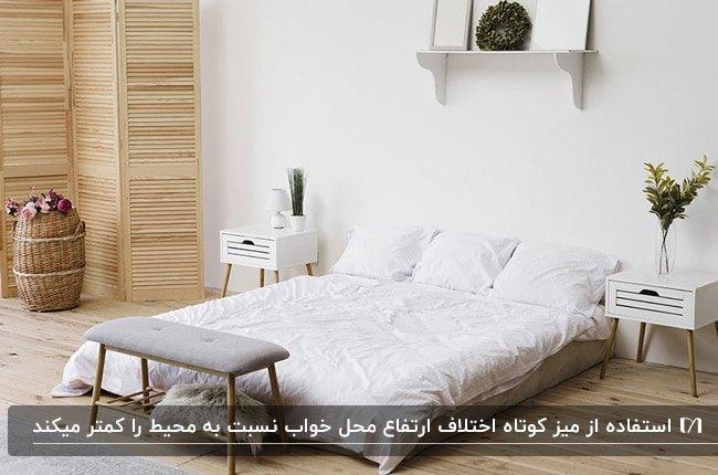 اتاق خواب سفیدی با پارتیشن چوبی و میز کوچک سفید کنار تشک