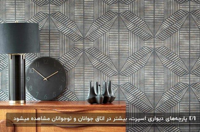 پارچه دیواری طرحدار خاکستری با کنسول چوبی و آباژور مشکی