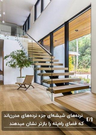 خانه مدرنی با راه پله چوبی به همراه نرده شیشه ای و یک صندلی تاشو رنگ چوب زیر پله