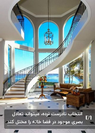 خانه ای با دیوار منحنی شیشه ای، راه پله منحنی با نرده های فلزی و مبلمان زیر پله